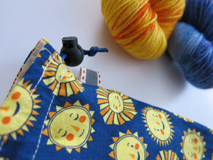 happy cartoon suns on a handmade project bag for sock knitting