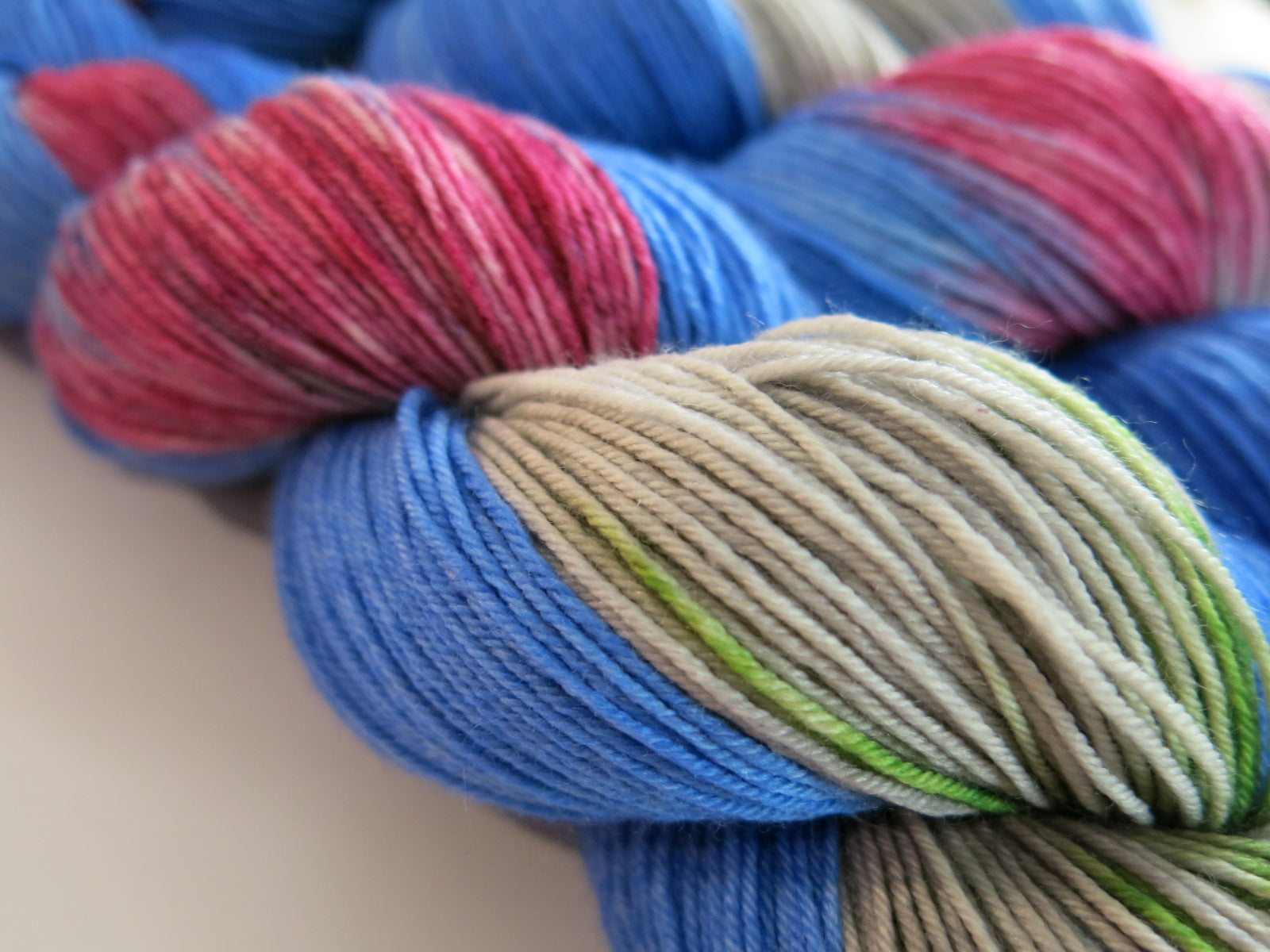 indie dyed sock yarn skeins in blue, pink, green and grey