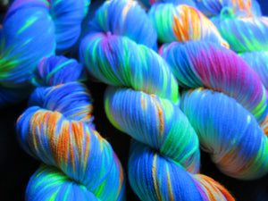 uv reactive sock yarn skeins with pink orange and yellow