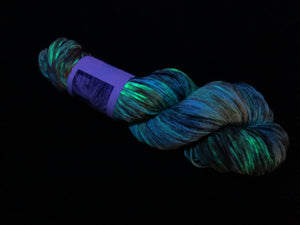 hand dyed uv reactive yarn under black light by my mama knits
