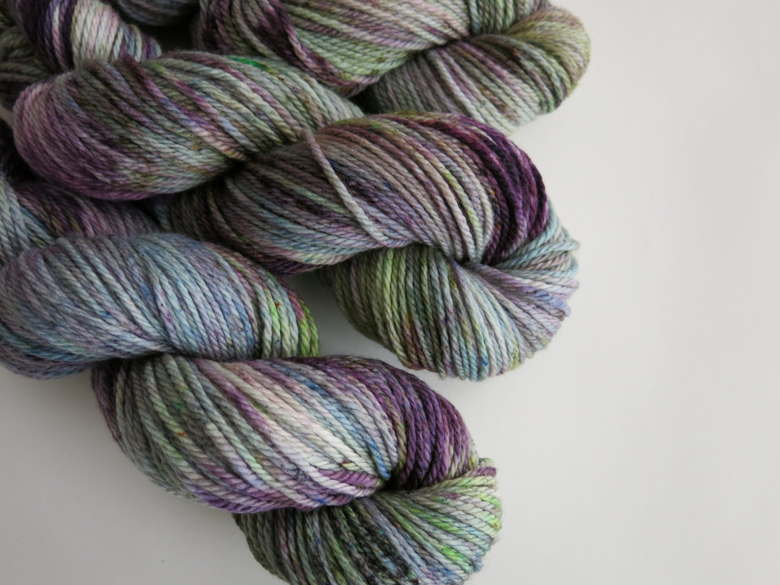 green and purple merino wool skeins for knitting, weaving and crochet