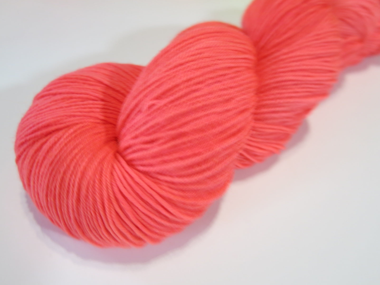 hand dyed neon coral black light yarn by my mama knits