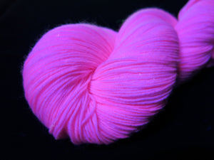 hand dyed solid light pink yarn fluorescing under uv black light