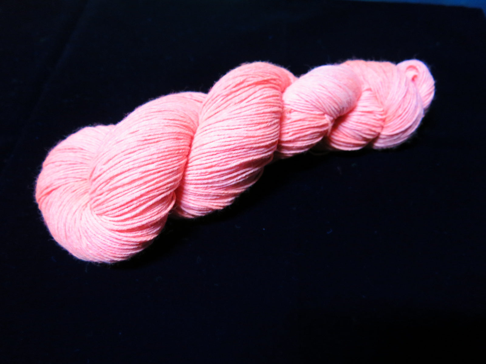 hand dyed solid coral orange yarn fluorescing under uv black light