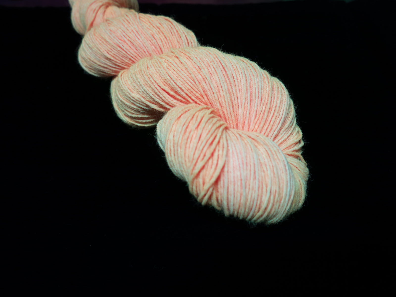 hand dyed solid orange yarn fluorescing under uv black light