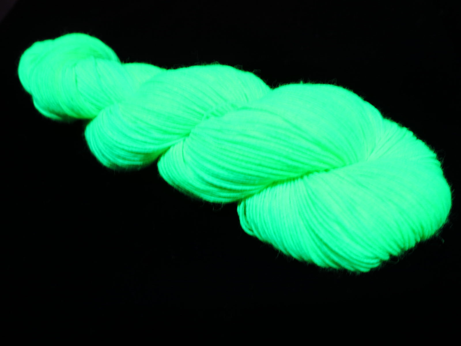 green uv reactive knitting yarn glowing under fluorescent blacklight