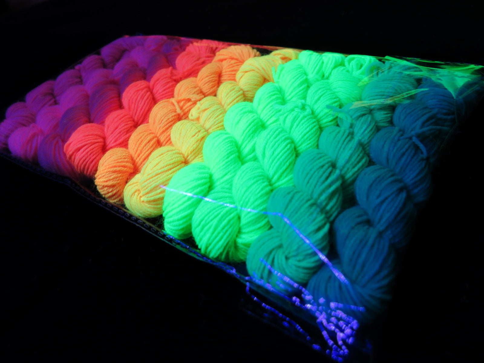 hand dyed uv reactive yarn mini skiens fluorescing under black light