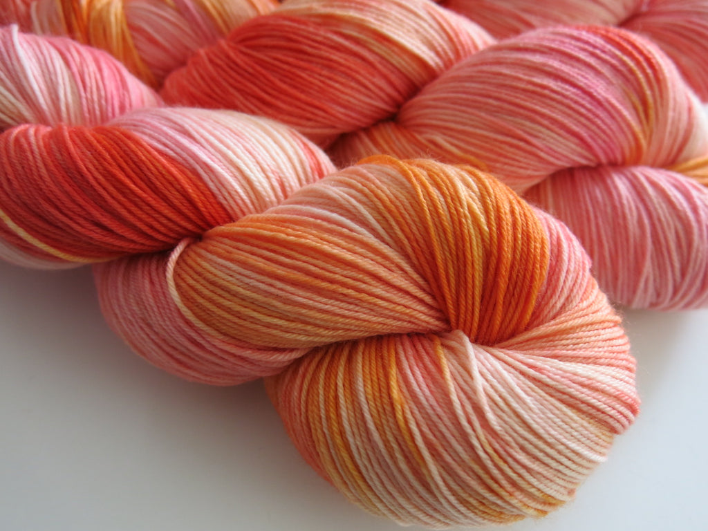 hand dyed pink and orange sock yarn skeins by my mama knits