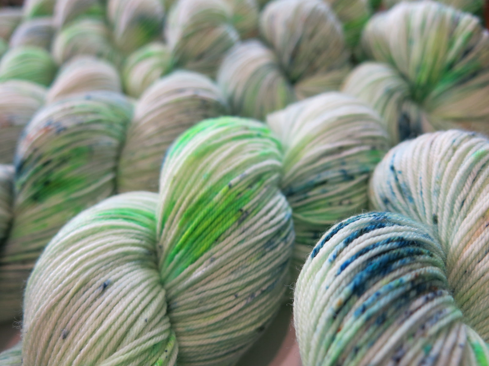 speckled uv reactive green yarn skeins for knitting, embroidery and crochet