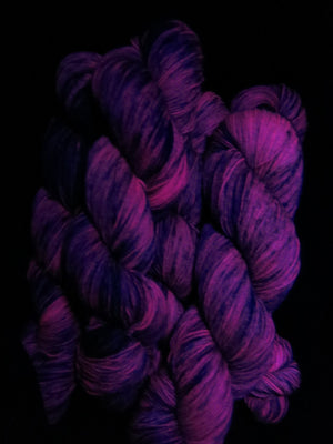 purple speckled sock yarn fluorescing under uv black light