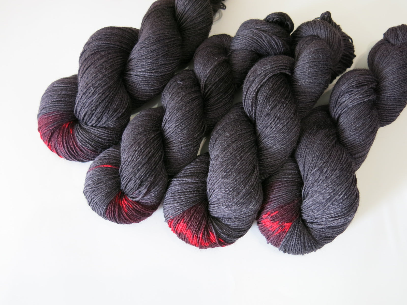 black yarn skein with a pop of red colour inspired by black widow spiders