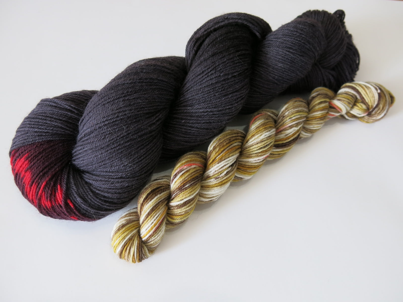 male and female black widow spider inspired sock yarn skeins for knitting