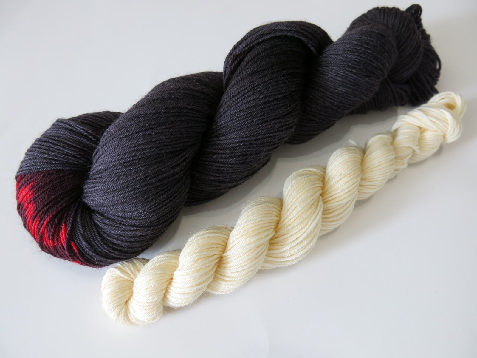 sock yarn skeins inspired by black widos and their ivory egg sacs