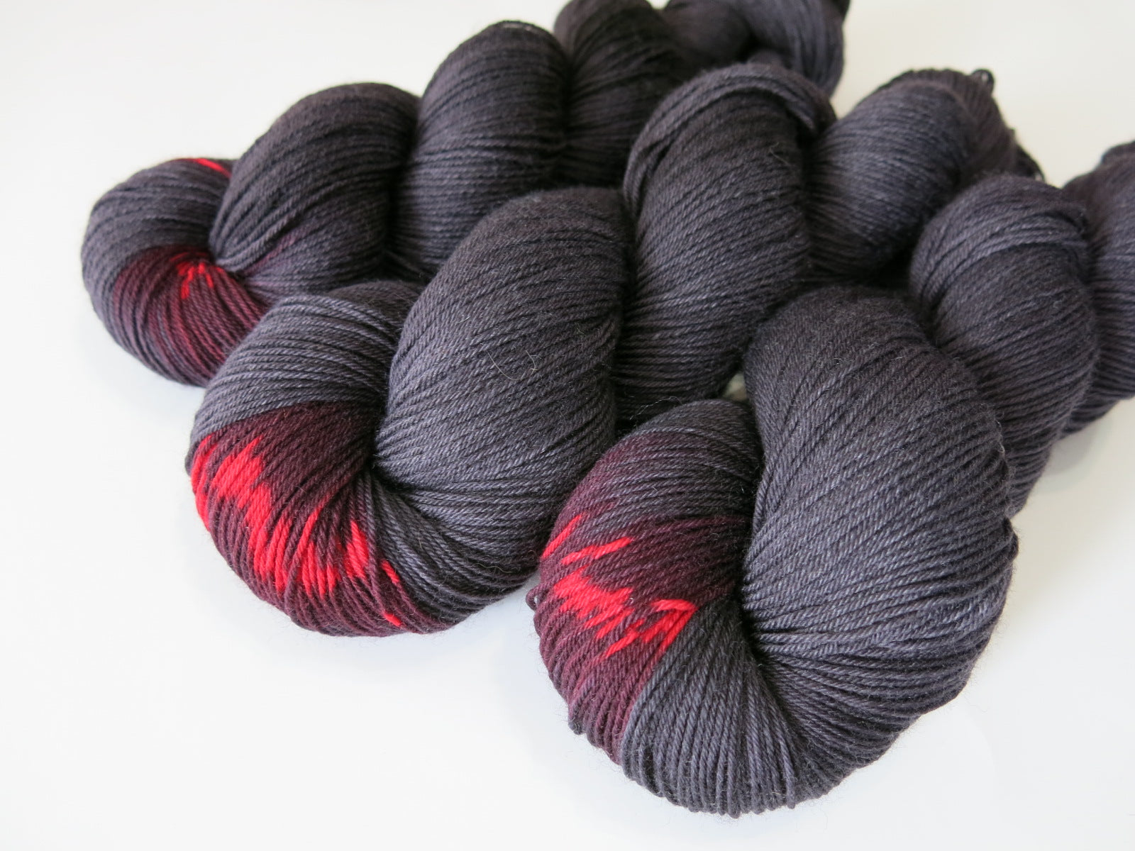 black sock yarn skein with a pop of red colour inspired by black widow spiders