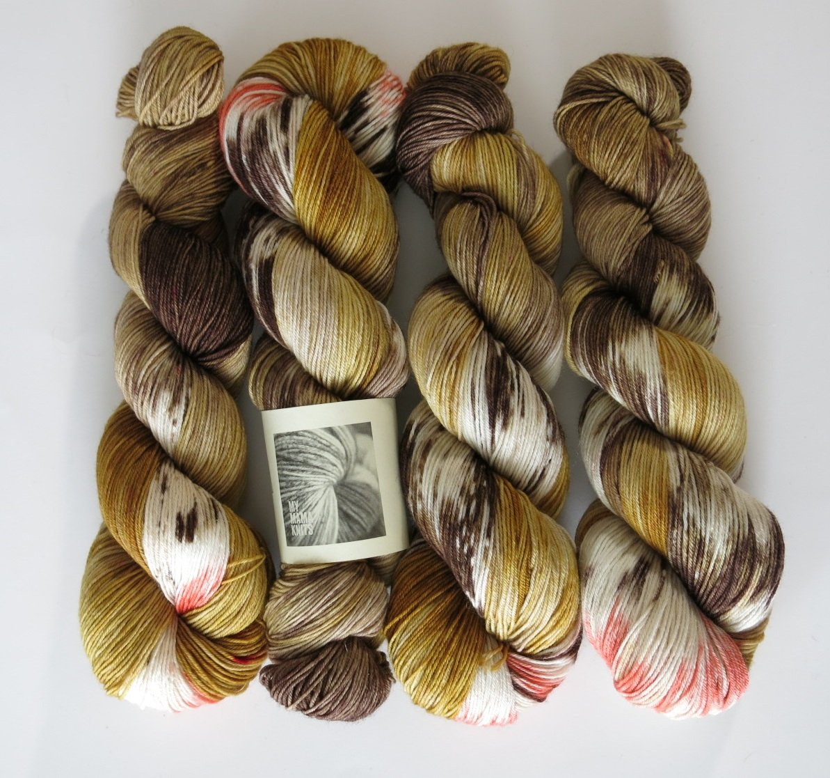 hand dyed yarn inspired by male black widow spiders in browns and coral