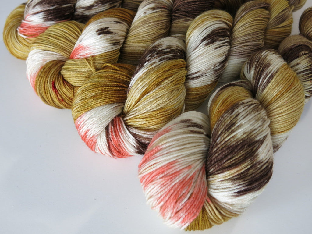 hand dyed yarn skeins in tan and brown with a pop of coral