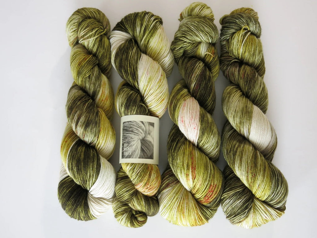 green and cream 4 ply sock yarn with red speckles like a trex