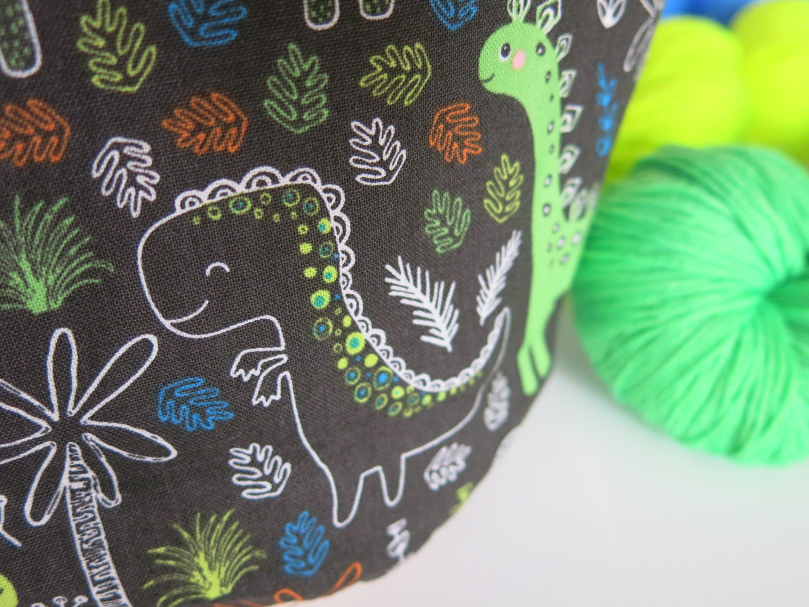 cotton drawstring knitting project bags with cartoon dinosaurs with a brown background