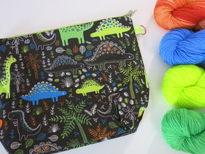 cotton zippered knitting project bags with cartoon dinosaurs with a brown background