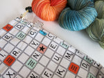 white cotton drawstring knitting project bag with a scrabble board game print