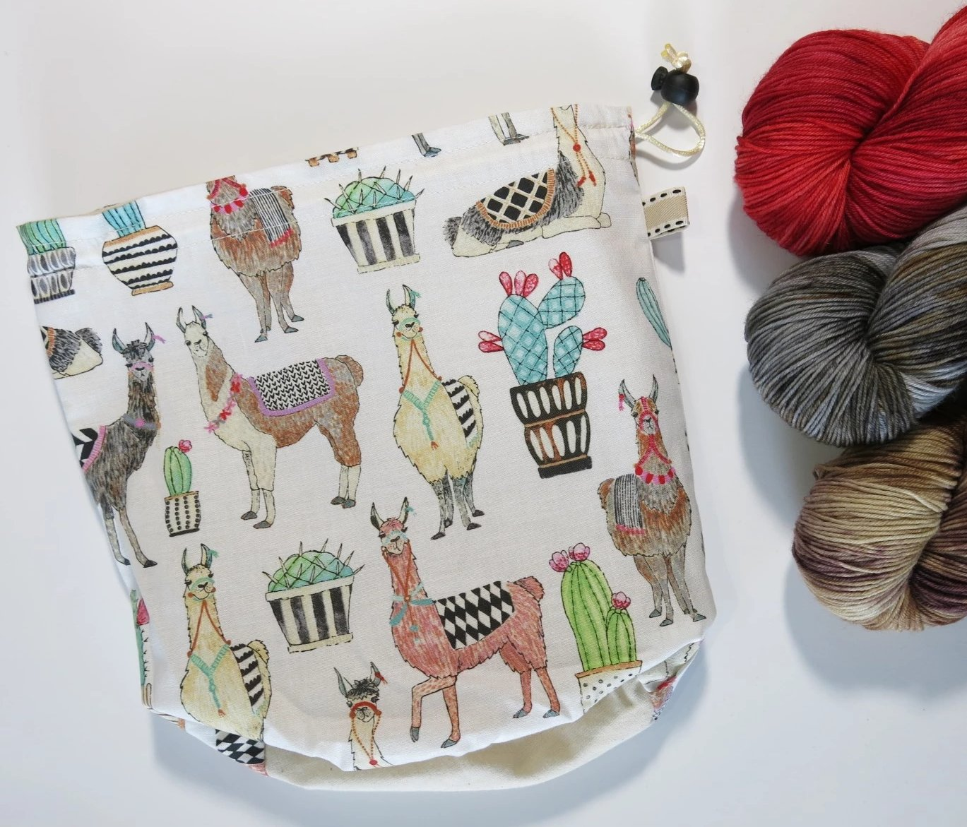 white cotton drawstring knitting project bag with llamas and cactus