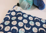dark blue cotton drawstring knitting project bag with smiling moon faces