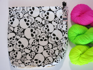 knitting project bag with skulls and neon yarn in pink yellow and green