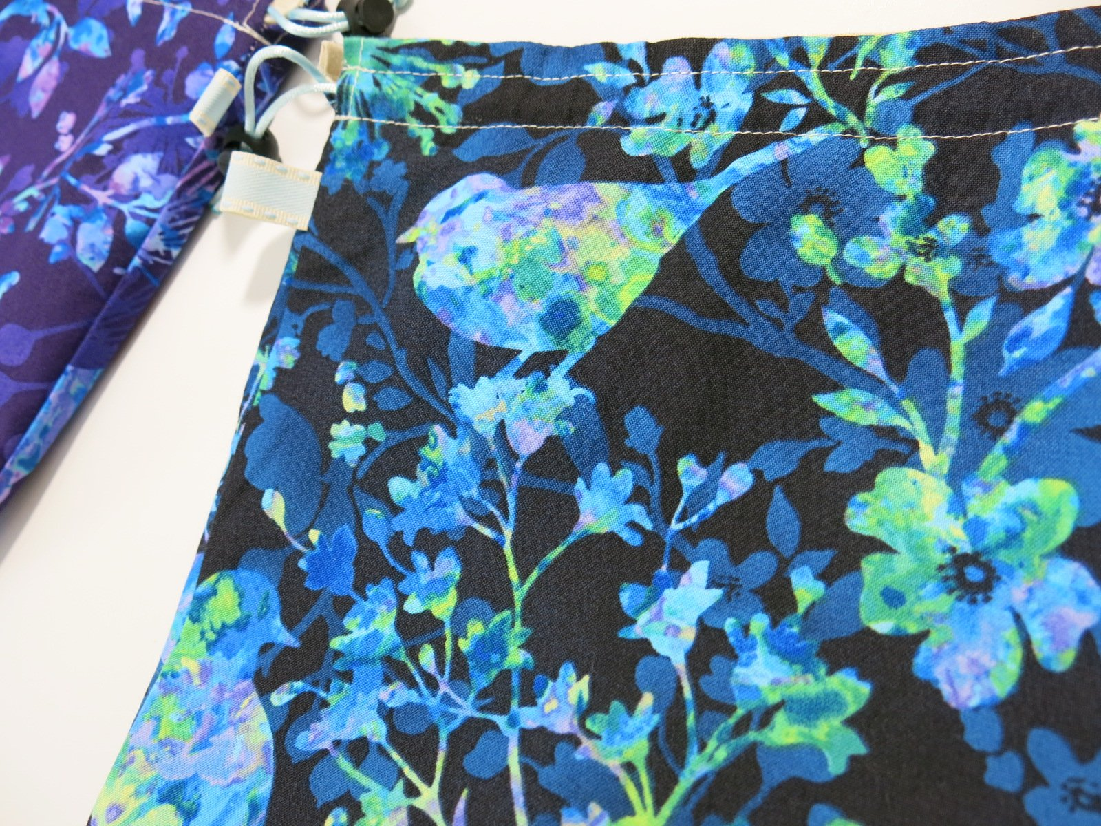 cotton drawstring knitting project bag with a batik bird and flower print in purple and blue