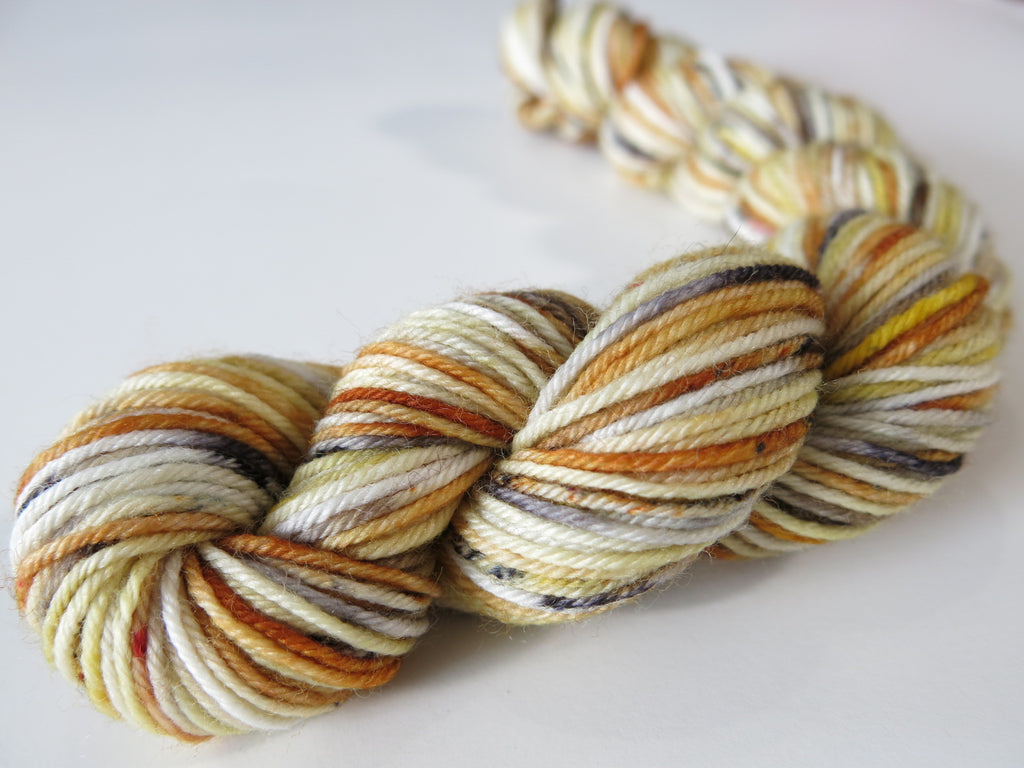 vareigated merino yarn mini skein in soft browns creams and blacks