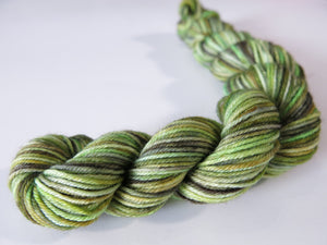 hand dyed sock yarn mini skein with multiple bright to mossy greens