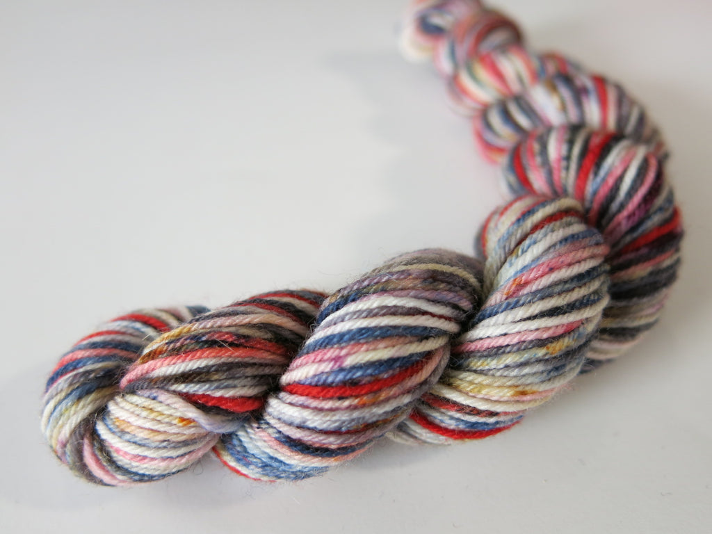 speckled red blue white and black sock yarn mini skein