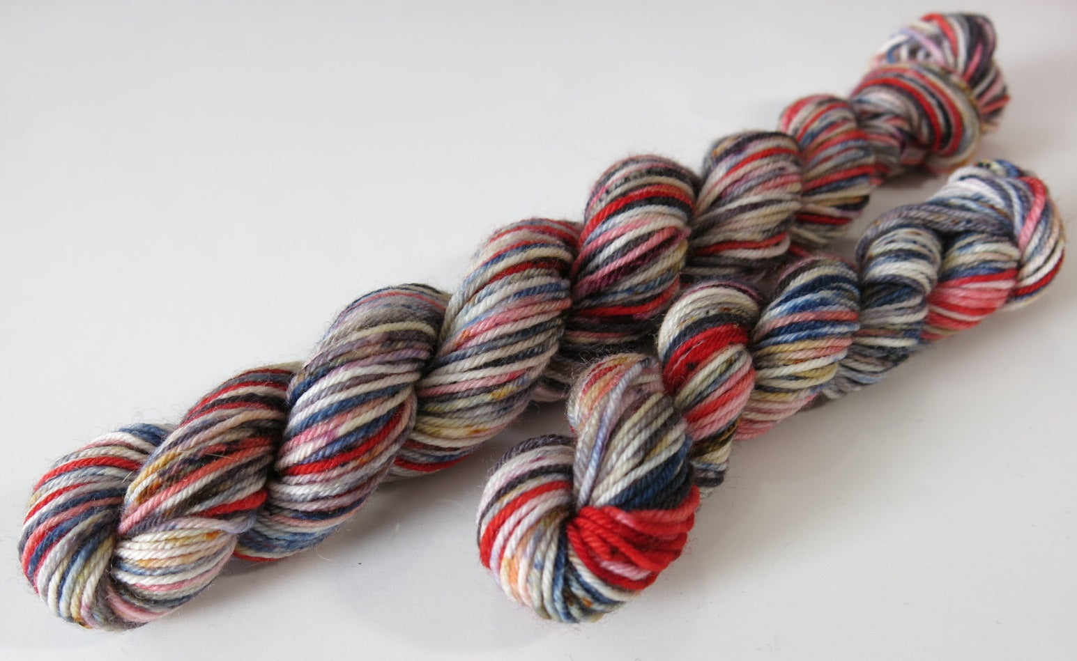 redcap inspired speckled red blue white and black sock yarn mini skein