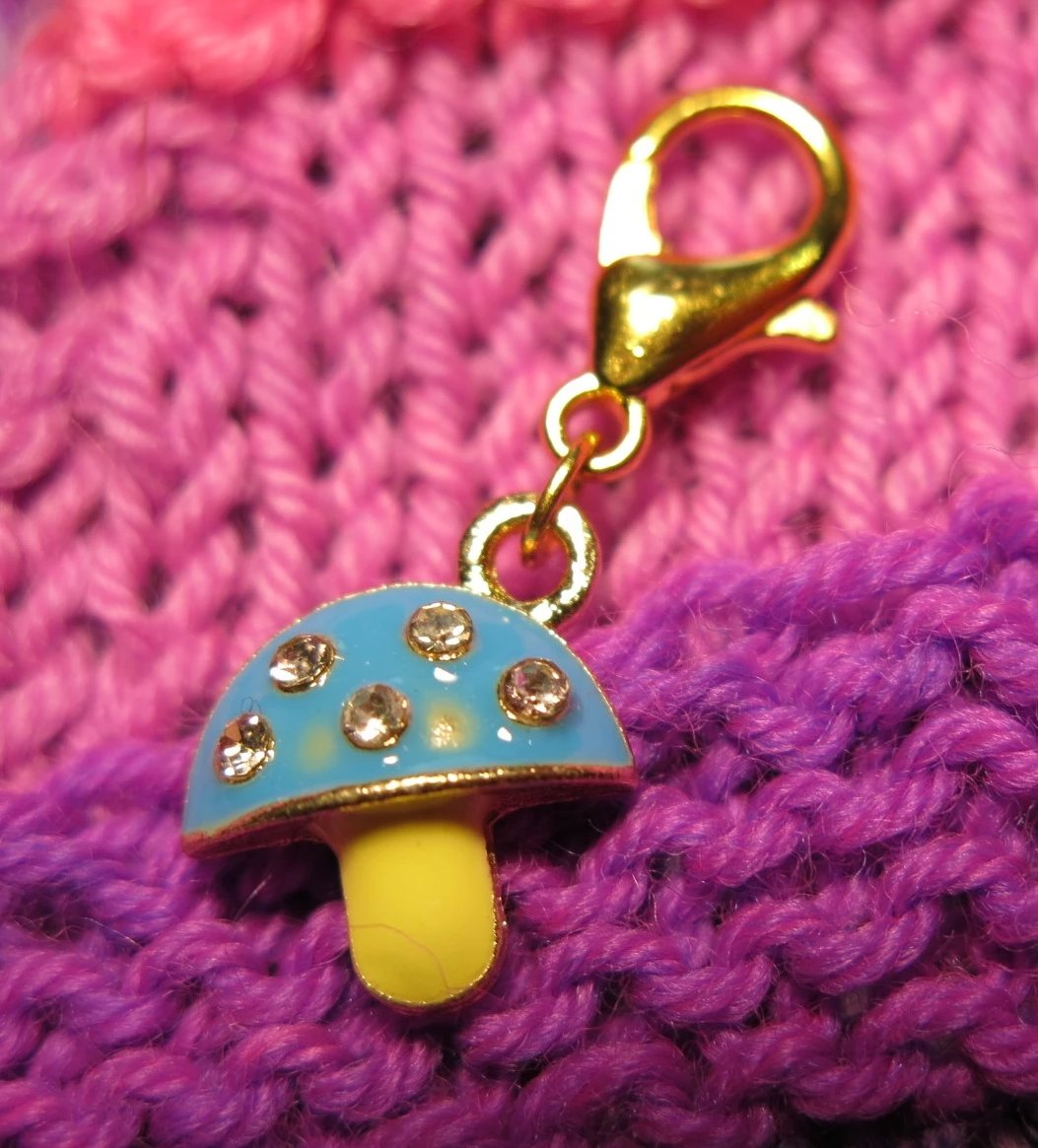 blue and yellow enamel mushroom stitch marker with rhinestones on a lobster clasp