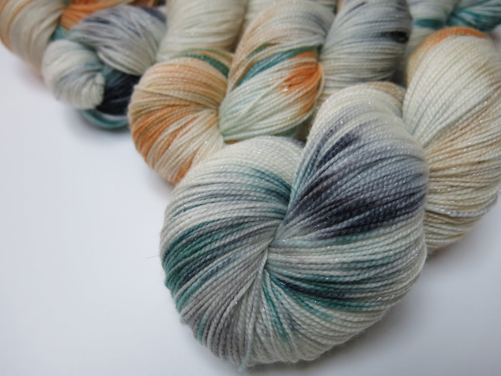 sparkly 4 ply sock yarn skeins with blue, tan and grey on white