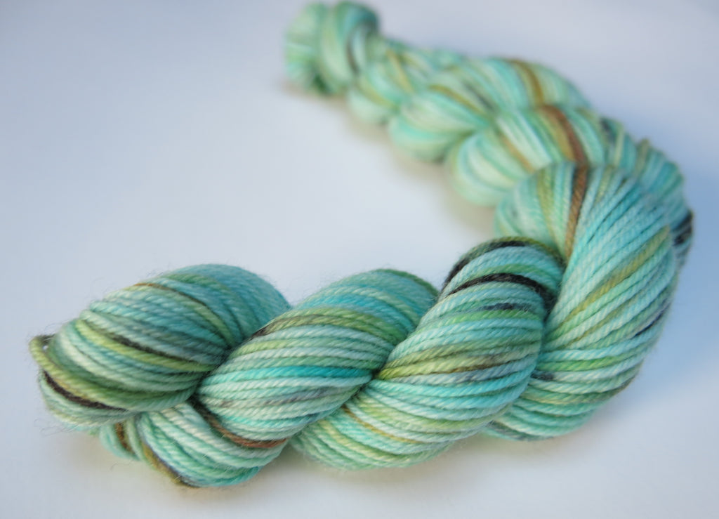 20g sock yarn mini skein in light turquoise with black and golden speckles