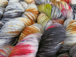 hand dyed yarn with black speckles and fire reds and yellows