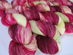 red moss inspired sock yarn in deep pinks yellowy greens and maroon