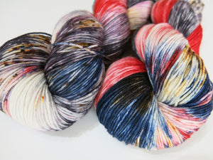 hand dyed red, blue and white yarn skein with black and grey speckles