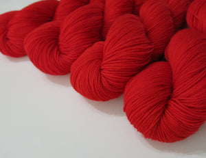 magic ribbon hand dyed solid red superwash merino sock yarn skeins