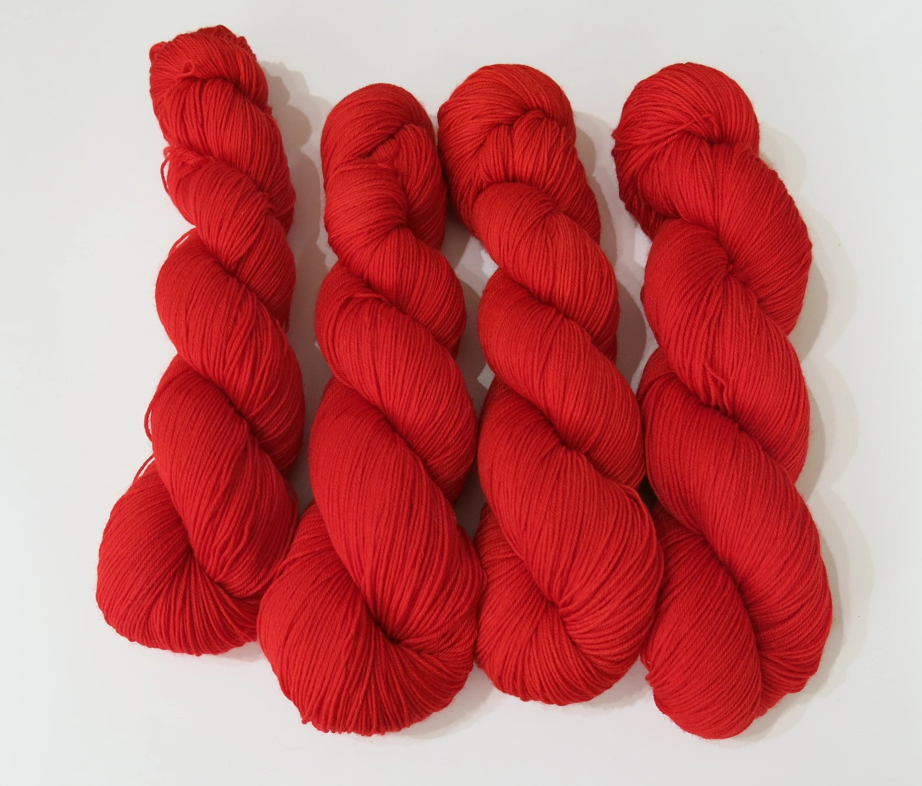 hand dyed solid red superwash merino sock yarn skeins