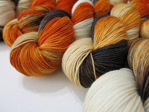 hand dyed merino sock yarn with fox reds black and creams