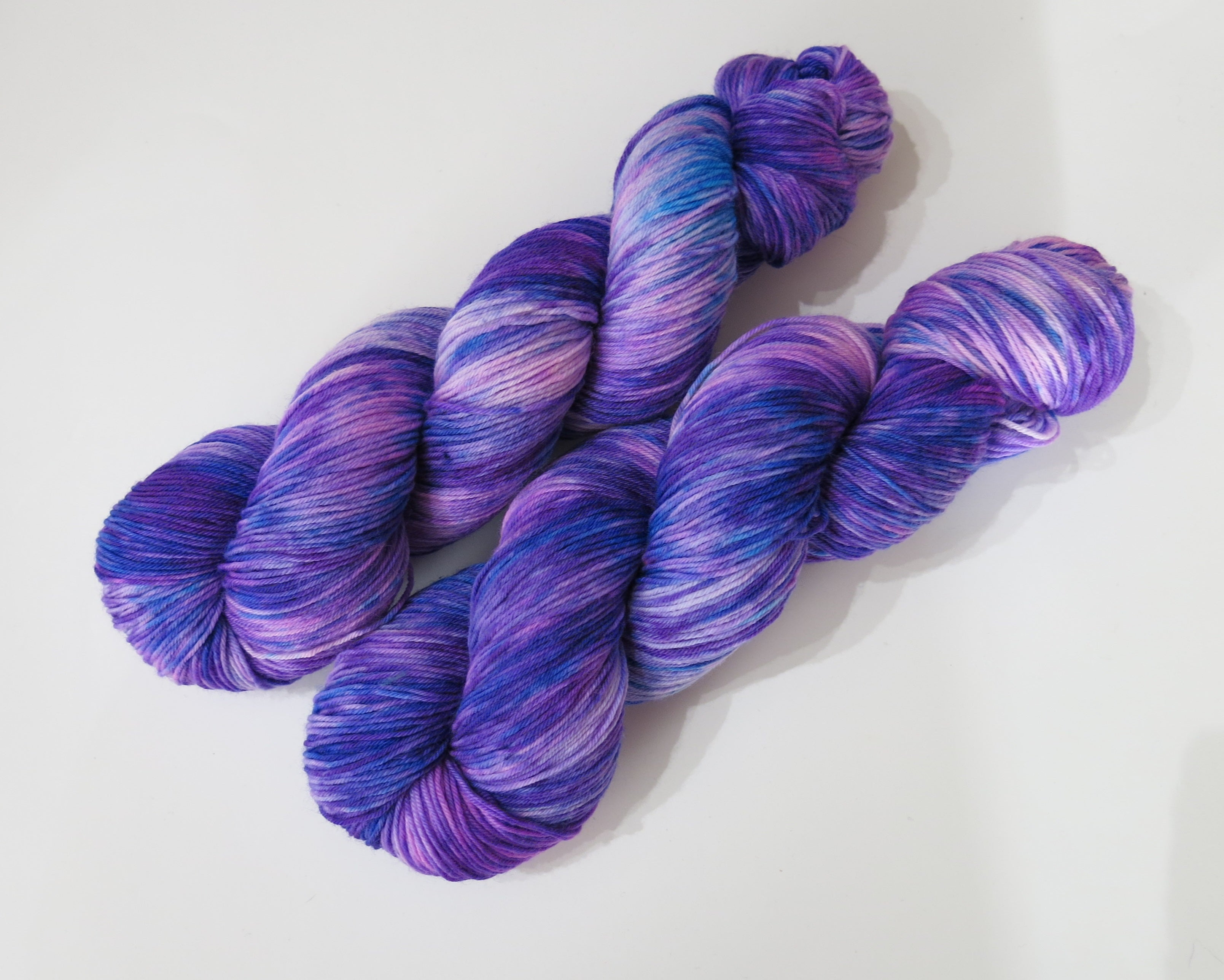hand dyed purple pink and blue vareigated sock yarn skeins