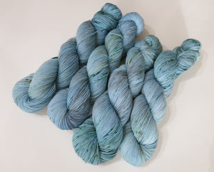 light blue sock yarn skeins with green speckles