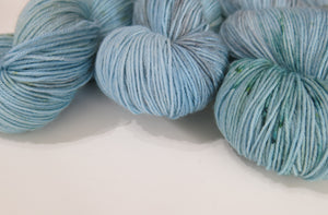 pastel blue sock yarn skeins with green speckles