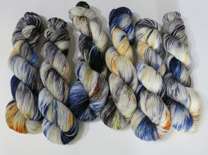 indie dyed yarn with specles and black and blue pools of colour