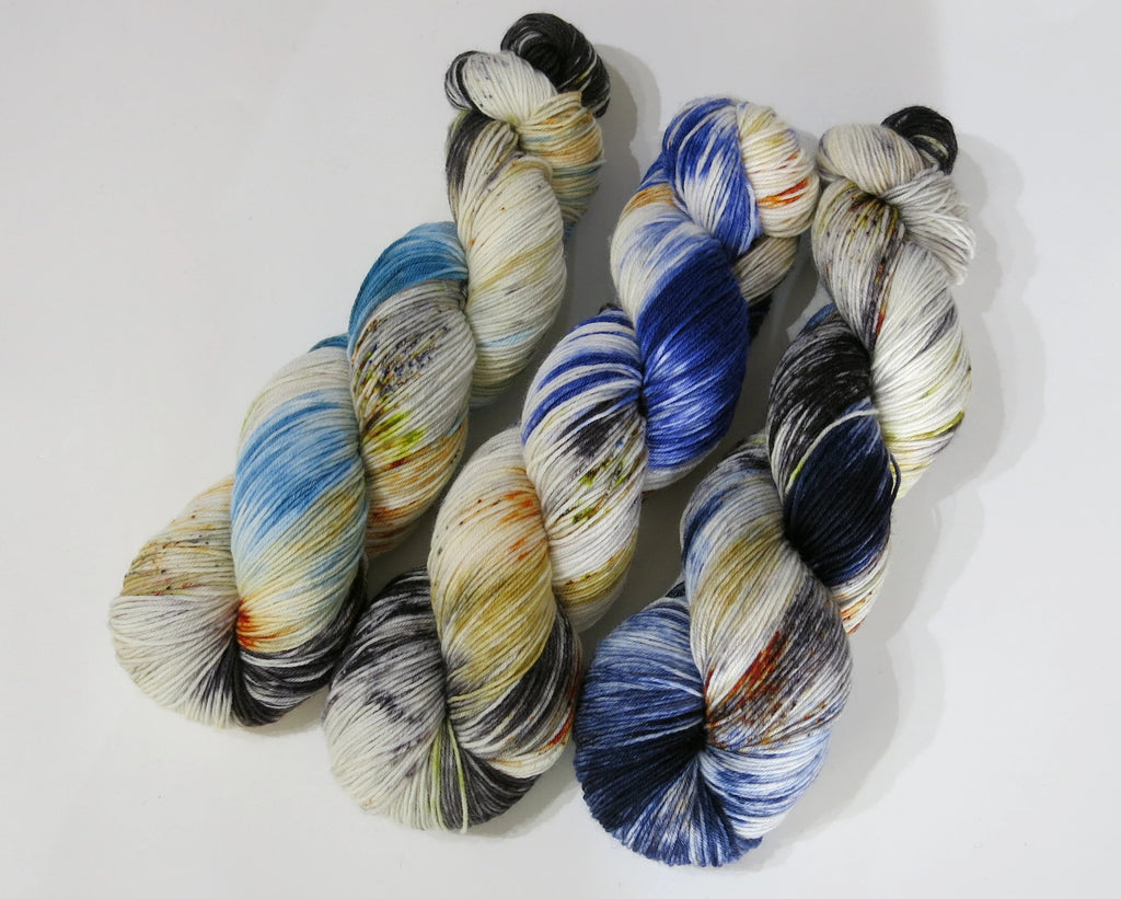 three speckled black and blue sock yarn skeins in a gradient