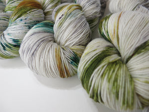 well of youth handdyed by my mama knits light grey yarn with green speckles