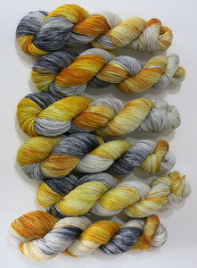 indie dyed superwash sock yarn skeins in golds and greys