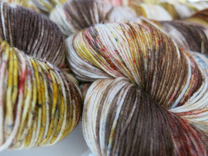 indie dyed grey and brown sock yarn skeins with brown and red speckles