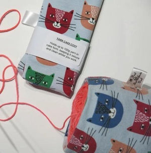 yarn cake cosy with solid coloured cat cartoon faces on a pale blue background